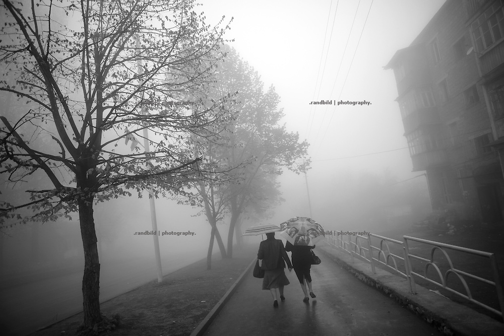 "A street scene on a foggy day in Shushi. This image is part of the photoproject ""The Twentieth Spring"", a portrait of caucasian town Shushi 20 years after its so called ""Liberation"" by armenian fighters. In its more than two centuries old history Shushi was ruled by different powers like armeniens, persians, russian or aseris. In 1991 a fierce battle for Karabakhs independence from Azerbaijan began. During the breakdown of Sowjet Union armenians didn´t want to stay within the Republic of Azerbaijan anymore. 1992 armenians manage to takeover ""ancient armenian Shushi"" and pushed out remained aseris forces which had operate a rocket base there. Since then Shushi became an ""armenian town"" again. Today, 20 yeras after statement of Karabakhs independence Shushi tries to find it´s opportunities for it´s future. The less populated town is still affected by devastation and ruins by it´s violent history. Life is mostly a daily struggle for the inhabitants to get expenses covered, caused by a lack of jobs and almost no perspective for a sustainable economic development. Shushi depends on donations by diaspora armenians. On the other hand those donations have made it possible to rebuild a cultural centre, recover new asphalt roads and other infrastructure. 20 years after Shushis fall into armenian hands Babies get born and people won´t never be under aseris rule again. The bloody early 1990´s civil war has moved into the trenches of the frontline 20 kilometer away from Shushi where it stuck since 1994. The karabakh conflict is still not solved and could turn to an open war every day. Nonetheless life goes on on the south caucasian rocky tip above mountainious region of Karabakh where Shushi enthrones ever since centuries."