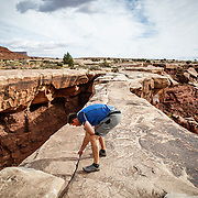 SHOT 10/17/16 10:35:01 AM - Mike Tryggestad of Denver, Co.spreads the ashes of friend Doug Pensinger atop Musselman Arch on the White Rim Trail. The White Rim is a mountain biking trip in Canyonlands National Park just outside of Moab, Utah. The White Rim Road is a 71.2-mile-long unpaved four-wheel drive road that traverses the top of the White Rim Sandstone formation below the Island in the Sky mesa of Canyonlands National Park in southern Utah in the United States. The road was constructed in the 1950s by the Atomic Energy Commission to provide access for individual prospectors intent on mining uranium deposits for use in nuclear weapons production during the Cold War. Four-wheel drive vehicles and mountain bikes are the most common modes of transport though horseback riding and hiking are also permitted.<br /> (Photo by Marc Piscotty / &copy; 2016)
