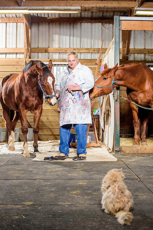 Gettysburg, Pennsylvania - February 06, 2017: Ron Krajewski assists Metro Meteor, left, with his paintings in the studio space adjacent to the the retired racehorse's stall at the Rickety Bridge Farm in Gettysburg, Pa.<br /> <br /> Metro Meteor's best friend Pork Chop looks for some attention from Ron. A barn cat sits by, seemingly unamused.<br /> <br /> <br /> Knee injuries put Metro Meteor in an early retirement, and left him unridable as a pleasure horse. Noticing his horse's affinity for head bobbing, he put a paint brush in his mouth and canvas in front. Metro Meteor's  paintings sold. Painting helped save his life, and helped save other horses' lives, too. Half the money from his paintings goes to New Vocations Racehorse Adoption Program and Gentle Giants Draft Horse Rescue.<br /> <br /> <br /> CREDIT: Matt Roth