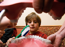 NEWS&GUIDE PHOTO / PRICE CHAMBERS.Wilson first grader Wyatt Sullivan, 7, learns the basics of tooth care with a very large set of chompers during a class trip to the dentist on Tuesday. 35 students recieved a crash course in dental health and a checkup courtesy of Dr. Rebecca Cloetta. She has been a dentist for 23 years, 11 in Jackson Hole and said that February is National Children's Dental Health Month.