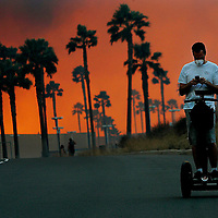 A Man usues his cellular phone while riding a Segway in a neighborhood in Yorba Linda California on Saturday. Strong Santa Ana winds are fanning flames throughout much of Southern California destroying hundreds of homes and causing thousands to evacuate.