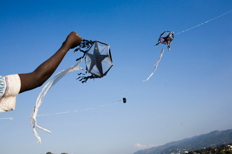 "Lukson Sevil flys a home-made kites on the edge of a temperary camp in Mon Ganye, Petionville, Haiti. 2/7/2010 photo by Ben Depp.                                      Bystander Emanuel Pierre say's ""everything is destroyed but we still have kites and wind, the children like it because flying kites helps them forget"""