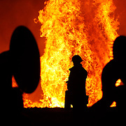 A pair of sousaphone players frame a Northport firefighter as he puts out fires around the outside of the bonfire during the Tuscaloosa County High School homecoming bonfire at the school in Northport Thursday evening, September 15, 2016.  Staff Photo/Gary Cosby Jr.