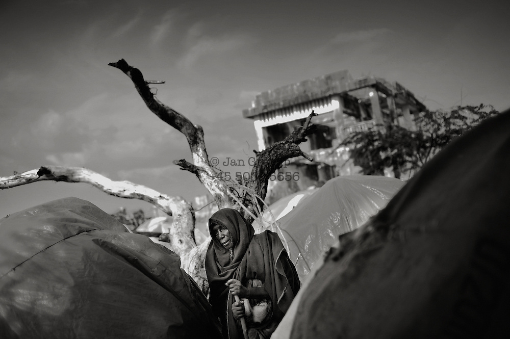 An old woman overlooking the Badbado IDP camp in the outskirts of the city. Badbado is the largest of the many IDP camps in the city. More than 200.000 refugees are believed to live in the city. Mogadishu;SomaliaThe Horn of Africa is facing a severe crisis due to the convergent effects of the worst droughts in decades, and the persistent effects of armed conflict in Somalia, which has combined to trigger one of the sharpest refugee outflows in a decade to Kenya and Ethiopia. Over ten million people are at high risk including 2.85 million persons in Somalia, 3.2 million in Ethiopia and 3.5 million in Kenya.&ndash;&ndash; Despite access and security limitations, UNICEF is working with local partners in Somalia to bring much-needed relief to over 200,000 people newly displaced by the recent upsurge in conflict in the capital, Mogadishu. - For hundreds of thousands of displaced Somali children, daily life is a mixture of fear and insecurity. Communities break apart, as one by one families leave their villages to flee ongoing conflict. If they survive the journey to Mogadishu, life is not much easier, as they are faced with the daily challenge of finding food and shelter.<br /> For children, this experience can be traumatizing. Having fled their homes in search of safety, they find themselves in overcrowded camps, away from all they know.<br /> While most children arrive in the displaced camps with their families, some are tragically separated from their parents and are either left to fend for themselves or forced to rely on already overburdened community members. Each Child Friendly Space has facilitators from UNICEF&rsquo;s NGO partners who work with the children. Several of the partners also have social workers to help identify and refer children in need of care and protection to the appropriate services.