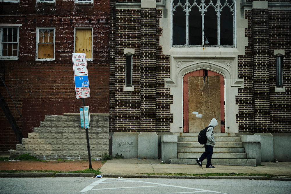Photo copyright 2009, Matt Roth<br /> Wednesday, February 29, 2012<br /> <br /> A student walks past a dilapidated building on Caroline Street in Baltimore, MD, Wednesday, February 29, 2012. The neighborhood, which has three government housing complexes, has two schools, the Baltimore Freedom Academy and City Springs Elementary/Middle School. While both are charter schools, the latter serves mostly neighborhood students. Ninety-six percent of City Springs' student body receives free lunches.