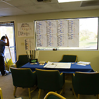 A janitor with bucket and mop pushes through the tournament scoring area.