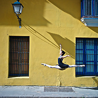 Professional classic ballerina from the Cuba National Ballet leaps in the colonial streets of old Havana.