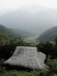 Landscape of a valley by a smooth foggy morningI. In foreground, a stilt house with leaves roof have a wonderfull sight on the national park. Pu Luong area, Hoa Binh province, Vietnam,Asia.