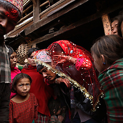 Sumeena Shreshta Balami, 15, cries as her father, Kainla Shreshta Balami, carries her to the front of the wedding procession, which will transport her to her new husband's home in Kagati Village, Kathmandu Valley, Nepal on Jan. 24, 2007. Early marriage is a harmful traditional practice common in Nepal. The Kagati village, a Newar community, is most well known for its propensity towards this practice.