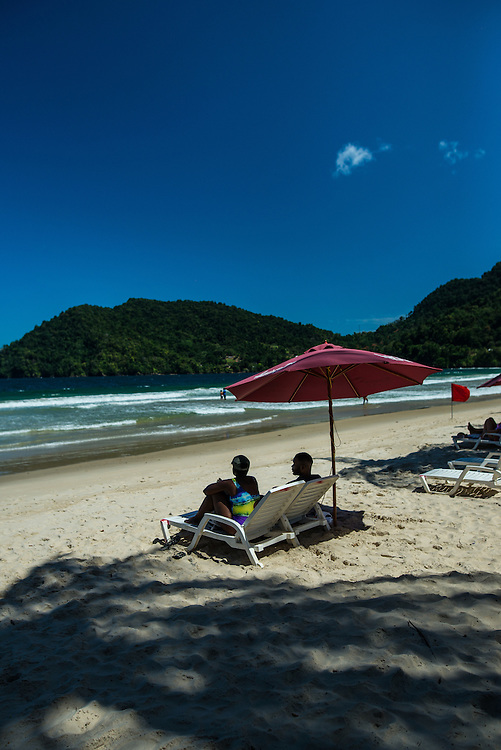 MARACAS BAY, TRINIDAD - FEBRUARY 14, 2017: Palm trees line the beach at Maracas Bay, the most popular beach within reach of the capital where crowds of people flock to go swimming in the clean, warm sea backed by lush green hills.  PHOTO: Meridith Kohut for The New York Times