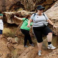 Guests Jerry Murray (L) Freyja Pereira (C)  and Martha Moore scramble over boulders on a hike through the rugged terrain at the Biggest Loser Resort in Ivins, Utah September 7, 2010.  Guests at the resort affiliated with the popular reality television show hike several miles each day and are restricted to a daily 1,200 calorie diet and exercise in gyms and pool for 6 to 7 hours a day.  REUTERS/Rick Wilking (UNITED STATES)