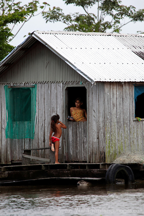 South America, Brazil, Amazon. A girl holds one leg as she talks to her mother, a scene of life on the Amazon.