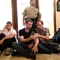 Brian Baumgardner,R, and Michael Anderson text during a sit-in for Gay Marriage at the SD County Clerk's office on Thurs., Aug. 19, 2010