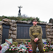 A man dressed with a ‪Canadian Expeditionary Force‬  officers uniform standing in front of the Beaumont-Hamel Newfoundland Memorial. On the back are the three bronze tablets that carry the names of 820 members of the Royal Newfoundland Regiment, the Newfoundland Royal Naval Reserve, and the Mercantile Marines who died in the First World War and have no known grave. The Caribou Memorial, the emblem of the Royal Newfoundland Regiment, standing atop a mound of Newfoundland granite. Beaumont-Hamel Newfoundland Memorial is dedicated to the commemoration of the Newfoundland Regiment that fought in the battle of Somme and WWI in general. Most of the  Newfoundland Regiment were dead within 15 to 20 minutes of leaving their trench in the morning of the 1st July 1916 during the first day of the Battle of the Somme.