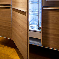 Lit up fridge interior with wooden door and wooden kitchen units