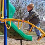 A small boy climbs up a ladder on an outdoor playscape.