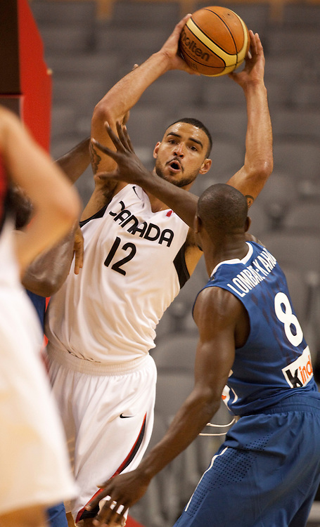 GJR506.jpg -20100812- Toronto, Ontario,Canada<br /> Canada's Robert Sacre throws a pass over France's Charles Lombahe-Kahudi during their game August 12, 2010 in the 2010 Jack Donohue International Classic tournament in Toronto, Canada . Canada defeated France 69-58.<br /> AFP PHOTO/Geoff Robins