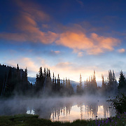 Steam rises at sunrise from one of the Reflection Lakes in Mount Rainier National Park, Washington.