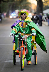 09 February 2016. New Orleans, Louisiana.<br /> Mardi Gras Day. A man dressed in costume rides the parade route along St Charles Avenue in the early morning hours. The main Mardi Gras Parades of Zulu and Rex pass by later in the day.<br /> Photo&copy;; Charlie Varley/varleypix.com