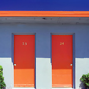 Texas motel detail with orange trim,shrubs, and deep blue sky.
