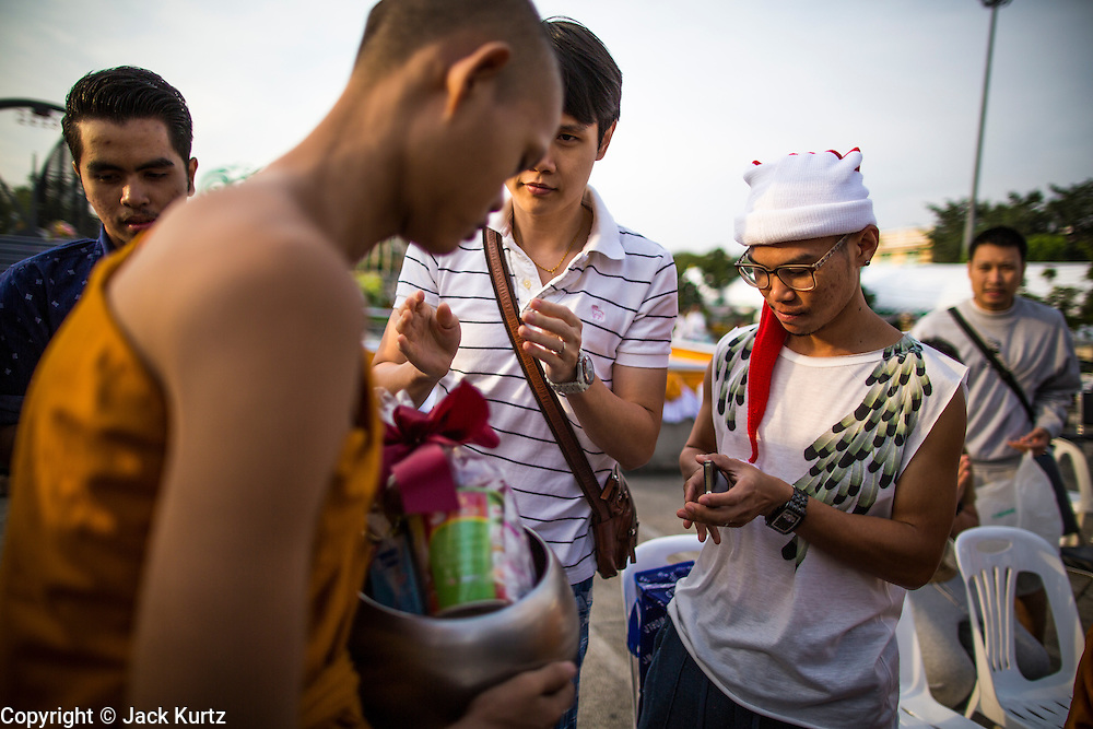 "01 JANUARY 2013 - BANGKOK, THAILAND:  A Thai teenager in a Santa hat presents a Buddhist monk with an offering during a special merit making ceremony at Bangkok City Hall New Year's morning. Many Thais go to Buddhist temples and shrines to ""make merit"" for the New Year. The traditional Thai New Year is based on the lunar calender and is celebrated in April, but the Gregorian New Year is celebrated throughout the Kingdom.     PHOTO BY JACK KURTZ"