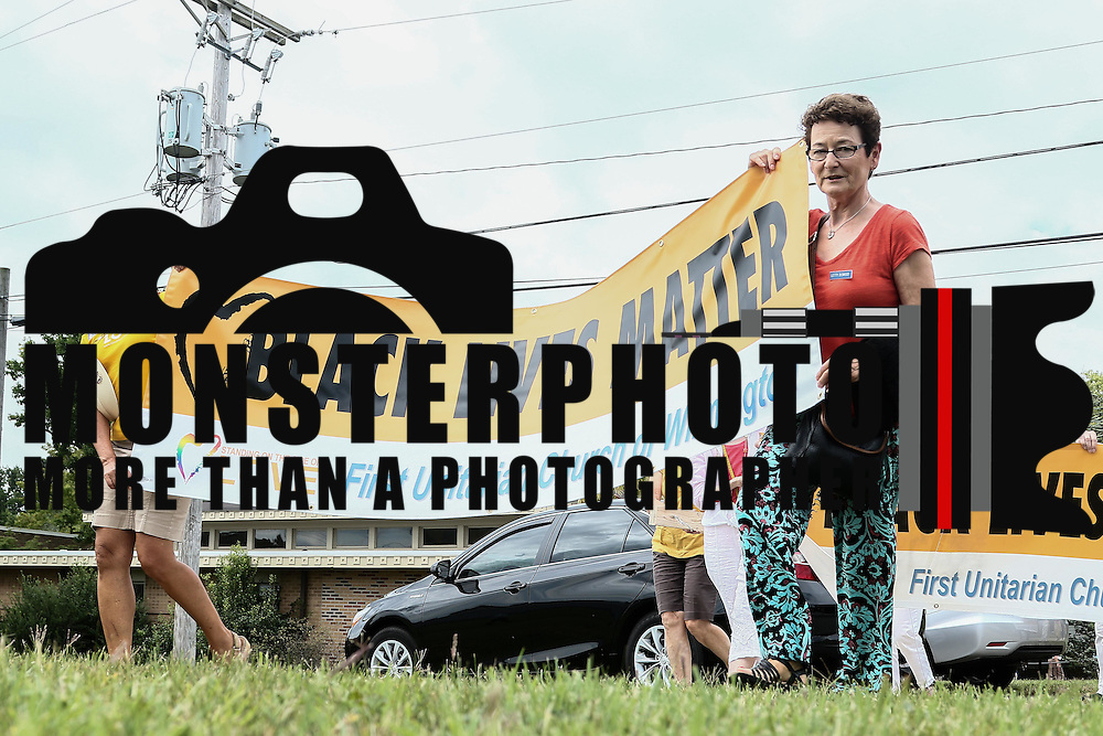 Members of the First Unitarian Church congregation march  towards Concord Pike while holding a black lives matter banner during a rededication ceremony Sunday, August 21, 2016, at First Unitarian Church in Wilmington.