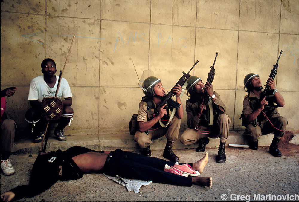 IPMG0045 South Africa, johannesburg 1994..A dead Zulu supporter of Inkatha after a downtown battle when Inkatha Freedom party members tried to storm the ANC's headquarters Shell House.  Several Zulus were killed, and it became known as the Shell House Massacre, downtown Johannesburg, 1994. The shoes are taken off to allow the soul to enter the afterlife unpolluted by dirt. .Photograph by Greg Marinovich/South Photographs
