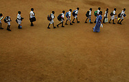 """Children follow their teacher as they head back to school, on the first day back to classes after the tsunami in the town of Panadura, Sri Lanka Monday Jan. 10, 2005.  Some 8,000 children will start lessons in makeshift school rooms _ some in tents pitched near their destroyed schools, some in buildings that did not fall and some using emergency """"school-in-a-box"""" kits provided by UNICEF consisting of exercise books, pencils, chalk, teaching aids and some puzzles."""