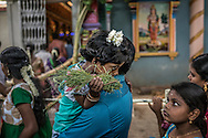 Young girl with jasmine flowers in her hair holds her sister's gaze as they wait to enter the Arulmiga Manakula Vinayagar Temple during Ganesh Chaturthi Festival.  Pondicherry, India.