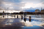 A cyclist silhouette is reflected in a puddle on the Place des Invalides in Paris after a storm