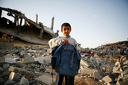 A boy holds his backpack found in the rubble of his family's home in Jabaliya, which was destroyed by Israel.