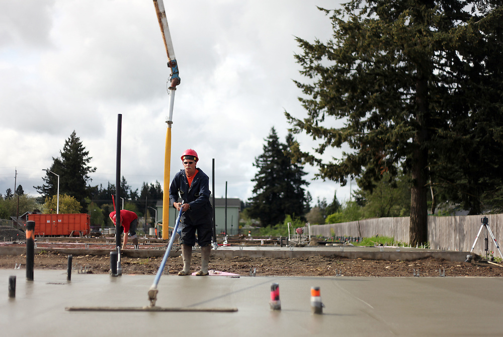 Emil Kinonen smooths freshly poured concrete on the Habitat site...John Gray was born 92 years ago and grew up poor in rural Oregon. He made a fortune in the chainsaw industry after World War II, and now he has donated more than a million dollars to Habitat for Humanity to buy land in Portland for low-income housing. Volunteers work to build solid foundations on the largest of these land parcels on Wednesday, May 2, 2012.