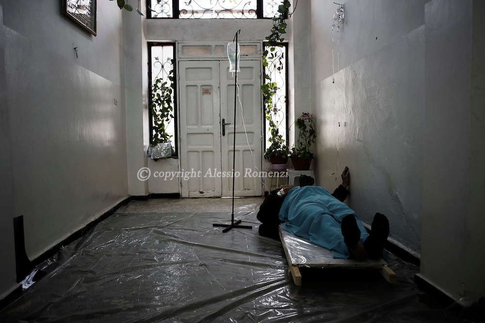 SYRIA - Homs province: A patient lies down in the entrance of a house used as hospital in Homs province on February 22, 2012. ALESSIO ROMENZI