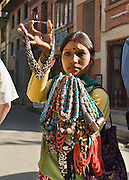 """A woman sells necklaces (some made of bone) in Patan's Durbar Square, Nepal, Asia. Patan was probably founded by King Veer Deva in 299 AD from a much older settlement. Patan, officially called Lalitpur, the oldest city in the Kathmandu Valley, is separated from Kathmandu and Bhaktapur by rivers. Patan (population 190,000 in 2006) is the fourth largest city of Nepal, after Kathmandu, Biratnagar and Pokhara. The Newar people, the earliest known natives of the Kathmandu Valley, call Patan by the name """"Yala""""  (from King Yalamber) in their Nepal Bhasa language. UNESCO honored Patan's Durbar Square (Palace Square) as one of the seven monument zones of Kathmandu Valley on their World Heritage List in 1979. All sites are protected under Nepal's Monuments Preservation Act of 1956."""
