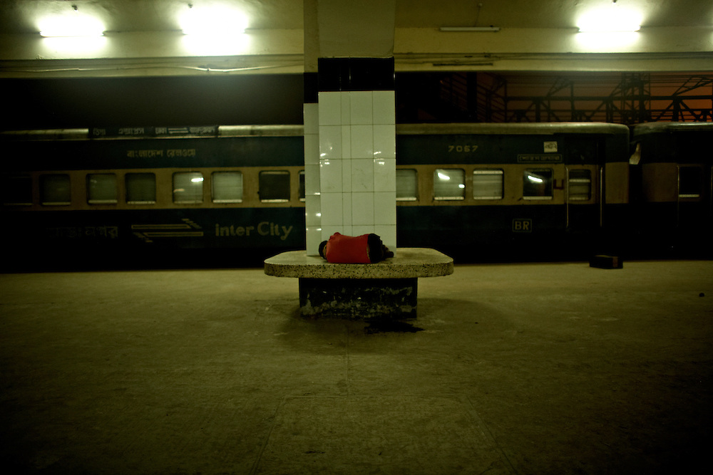Boy sleeping at Dhaka train station, Dhaka, Bangladesh...A boy is sleeping on the platform of Dhaka central station December 27, 2008.  Dhaka city is emptying as people are leaving to cast their vote in their respective home villages and districts...Bangladesh has finished with two years of emergency rule. The election results is compared to the landslide of 1970 that led to war and independence from Pakistan. .When preparations for the election started in late 2006, violent street-protests started, and led to a military backed interim government until the election happened under heavy security and watchful eyes on December 29th 2008...The past two years have seen a decrease of crime and corruption but also sparked violent student protests and curfews. Today  most people seem to be happy to return to some sort of normality. But in one of the poorest countries in the world where 80% live for less than a dollar a day, does it really matter who is in power? The circus is over, back to reality and putting food on the table...A blogger  from dhaka is quoted Ó we prefer messy democracy to military ruleÓ...Is this the end of night, a new dawn or yet another dusk?..Photo by: Eivind H. Natvig/MOMENT *** Local Caption ***