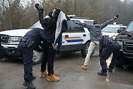February 25, 2017-Hemmingford, Quebec : RCMP officers search two members of a family of refugees from Djibouti who made an illegal crossing into Canada on Roxham Road.