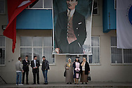 Kafkas University Graduate posing for photo under the Portrait of Ataturk and Turkish Flag.<br /> <br /> It is forbidden for woman to wear head-scarf at the territory of University.