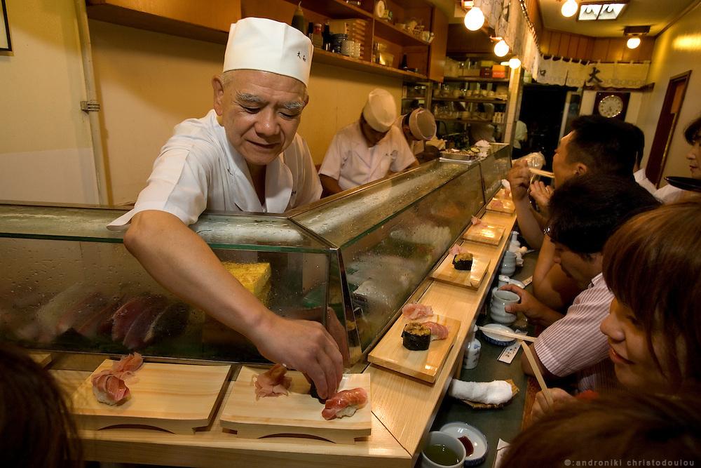 Chef Shinichi Irino (67) preparing sushi for the customers. Daiwa sushi is one of the most famous sushi restaurants of Tsukiji market. Tsukiji fish market  is the biggest wholesale fish and seafood market in the world and also one of the largest wholesale food markets of any kind. The market is located in Tsukiji in central Tokyo, and is a major attraction for foreign visitors.
