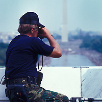 A policeman peers through binoculars atop the Lincoln Memorial scanning the crowd along the Reflecting Pool in Washington, DC in August 1983.