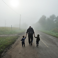 Syrian refugee father and chidlen on the move, as morning mist begins to clear, having passed by the collection point near R&ouml;szke where the Hungarian authorities require refugees to take buses to registration centres. If caught by poilice patrols they will be brought back.<br /> The sometimes chaotic and rubbish strewn collection point, with infrastructure, food and basic medical care provided only thanks to volunteers with support from UNHCR, is situated a kilometer inside the Hungarian frontier from Serbia, along an  old railway line, which thousands of refugees have used to cross the border. The flow of refugees continued to grow, with delays increasing, until the Hungarian government sealed the frontier with Serbia using razor wire and a high fence, and brought in new laws on the 15th September effectively halting the influx of refugees.