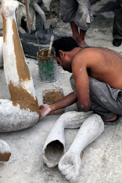 Asia, India, Calcutta. Sculptor works on limbs at the potter's village of Kumartuli in Calcutta.