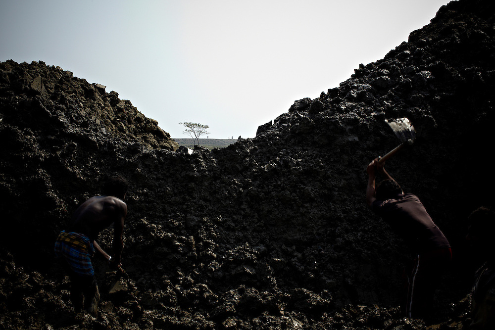 Workers dig out mud for a brick-factory in the foreground as a lone tree can be seen by the broken embankment on the shore of Meghna river...This area in the south of Bangladesh has been called ground zero of climate-change due to heavy river and ocean erosion. The lowlying area is also hugely affected by cyclones and rising sea-levels...By the Mouth of Ganges, at the Bay of Bengal is the Island of Bhola. This home of about two million people is considered to be ground zero of climate change. Half the island has disappeared in the past 40 years, and according to scientists the pace is not going to slow down. People pack up and leave as the water get closer. Some to a nearby embankment, while those with enough money move further inland, but for most life move on until the inevitable. It's always about survival for the people in one of the worlds poorest countries...Photo by: Eivind H. Natvig/MOMENT