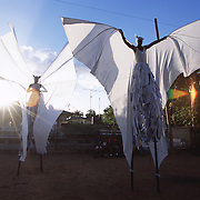 "Trinidad and Tobago ""MOKO JUMBIES: The Dancing Spirits of Trinidad"".(Rodney Barrow - right -, in his custom-made White Bat costume, deploys his fabric wings in front of John Sterling, who is testing his Jumbie Bat gear as the rays of the setting sun outline the stunning shapes of the twenty foot wingspan.).A photo essay about a stilt walking school in Cocorite, Trinidad..Dragon Glen de Souza founded the Keylemanjahro School of Art & Culture in 1986. The main purpose of the school is to keep children off the streets and away from drugs..He first taught dances like the Calypso, African dance and the jig with his former partner Cathy Ann Samuel.  Searching for other activities to engage the children in, he rediscovered the art of stilt-walking, a tradition known in West Africa as the Moko Jumbies , protectors of the villages and participants in religious ceremonies. The art was brought to Trinidad by the slave trade and soon forgotten..Today Dragon's school has over 100 members from age 4 and up..His 2 year old son Mutawakkil is probably the youngest Moko Jumbie ever. The stilts are made by Dragon and his students and can be as high as 12-15 feet. The children show their artistic talents mostly at the annual Carnival, which today is unthinkable without the presence of the Moko Jumbies. A band can have up to 80 children on stilts and they have won many of the prestigious prizes and trophies that are awarded by the National Carnival Commission. Designers like  Peter Minshall , Brian Mac Farlane and Laura Anderson Barbata create dazzling costumes for the school which are admired by thousands of  spectators. Besides stilt-walking the children learn the limbo dance, drumming, fire blowing and how to ride  unicycles..The school is situated in Cocorite, a suburb of Port of Spain, the capital of Trinidad and Tobago..all images © Stefan Falke"