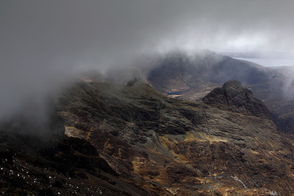 Cloud creeps over the summit of Bruach na Frithe, a munro within the Black Cuillin Hills in southern Skye, Scotland
