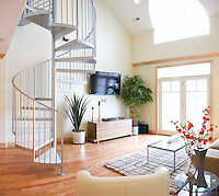 Open livingroom with light colors and lots of space, a spiral staircase and a balcony with a view.