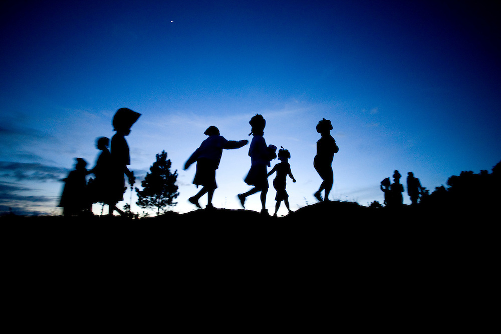 Women silhouetted against the night sky on thier way home after a food distribution.