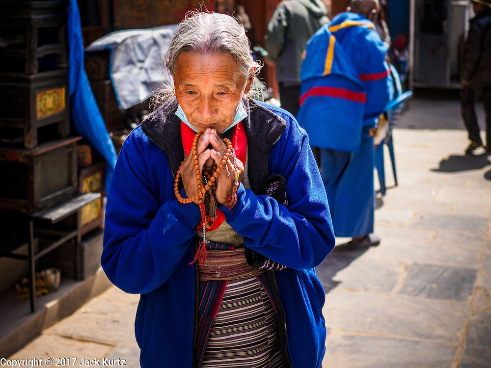 07 MARCH 2017 - KATHMANDU, NEPAL: A Nepalese Buddhist woman prays at the entrance to Boudhanath Stupa after the consecration ceremony at the Stupa. Boudhanath Stupa, the important Buddhist site in Nepal and a popular tourist attraction, was consecrated Tuesday in a ceremony attended by thousands of Buddhist monks and Buddhist people from Nepal and Tibet. The stupa was badly damaged in the 2015 earthquake that devastated Nepal. The stupa, which reopened in November 2016, was repaired in about 18 months. The repair was financed by private donations raised by international Buddhist organizations.     PHOTO BY JACK KURTZ