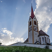 Rays of setting sun backlight the Parish Church of St. Nicholas (Nikolauskirche; dedicated to San Nicolò; consecrated in 1507), in Winnebach (Prato Drava) village, Sesto Dolomites, South Tyrol, Italy, Europe. For cheaper lodging in Val Pusteria (Pustertal), try Winnebach (Prato alla Drava) village near the Austrian border, beneath the Sexten/Sesto Dolomites (Italian: Dolomiti di Sesto; German: Sextener Dolomiten), in Trentino-Alto Adige/Südtirol (South Tyrol), Italy. Winnebach (Prato Drava) is in the comune (municipality) of Innichen/San Candido. The Dolomites are part of the Southern Limestone Alps, in Europe. UNESCO honored the Dolomites as a natural World Heritage Site in 2009.