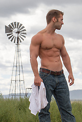 shirtless muscular man outdoors on a rural ranch