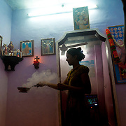 At dusk, incense is held around a house. In the neighborhood is a famous shrine to St. Anthony. Images and pictures of St. Anthony adorn many of the Catholic homes.